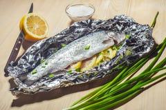 烘烤在一张木桌上的箔鱼 免版税库存图片