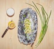 烘烤在一张木桌上的箔鱼 免版税库存照片