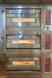 烘烤在烤箱的小圆面包在一个商业厨房里 库存照片