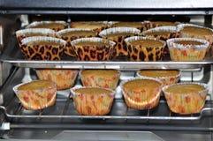 烘烤在烤箱的杯形蛋糕 库存照片