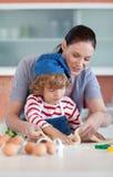烘烤执行母亲的儿童圣诞节 免版税库存照片