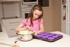 烘烤杯形蛋糕女孩厨房年轻人 库存照片