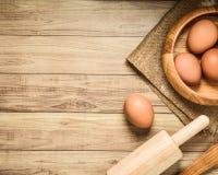 烘烤概念背景 厨房器物和烘烤成份:鸡蛋和面粉在木背景 库存图片