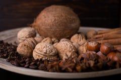 烘烤的成份,肉桂条,八角,丁香,坚果,椰子,在木背景的咖啡豆 库存图片