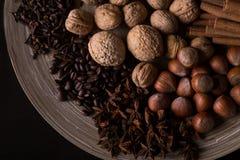 烘烤的成份,肉桂条,八角,丁香,坚果,椰子,在木背景的咖啡豆 免版税库存照片