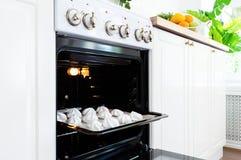 烘烤的盘子用在烤箱的甜蛋白甜饼在厨房 免版税图库摄影