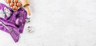 烘烤紫色礼物装饰鸡蛋和厨房用具在大理石桌上的圣诞节 免版税库存图片