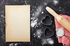 烘烤背景用面粉,滚针、纸板料和心脏在厨房黑色桌上从上面塑造为情人节 免版税库存照片