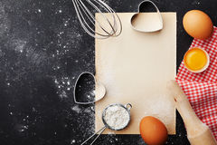 烘烤背景用面粉,滚针、鸡蛋、纸板料和心脏在厨房黑色桌上从上面塑造为情人节 免版税图库摄影