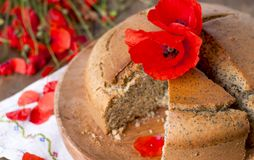 烘烤自创 与鸦片和柑橘的早餐蛋糕 红色鸦片花乡村模式和花束  木背景 复制 库存图片