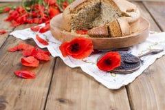烘烤自创 与鸦片和柑橘的早餐蛋糕 红色鸦片花和种子乡村模式和花束  木背景 库存照片