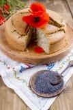烘烤自创 与鸦片和柑橘的早餐蛋糕 红色鸦片花和种子乡村模式和花束  木背景 免版税库存照片