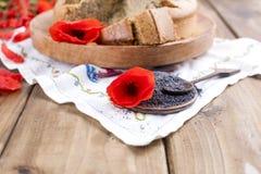 烘烤自创 与鸦片和柑橘的早餐蛋糕 红色鸦片花和种子乡村模式和花束  木背景 免版税图库摄影