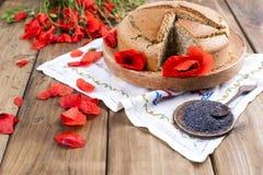 烘烤自创 与鸦片和柑橘的早餐蛋糕 红色鸦片花和种子乡村模式和花束  木背景 库存图片
