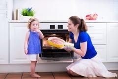 烘烤蛋糕的母亲和孩子 免版税库存图片