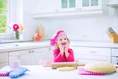 烘烤饼的逗人喜爱的小女孩 免版税库存图片