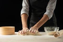 烘烤 供以人员准备面包、复活节蛋糕、复活节面包或者跨小圆面包在木桌上在面包店关闭  准备面包窦的人 图库摄影