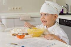 烘烤他喜爱的蛋糕的小男孩 图库摄影