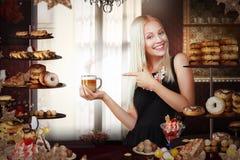 烘烤 有咖啡的愉快的女推销员在Bakeshop 库存照片