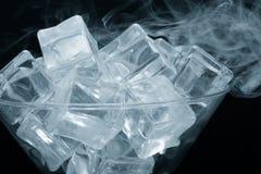 烟云在马蒂尼鸡尾酒玻璃的与在黑backgr的冰块 免版税库存图片
