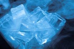 烟云在马蒂尼鸡尾酒玻璃的与在黑backgr的冰块 免版税图库摄影