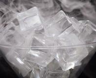 烟云在马蒂尼鸡尾酒玻璃的与在黑backgr的冰块 库存照片