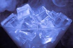 烟云在马蒂尼鸡尾酒玻璃的与在黑backgr的冰块 库存图片