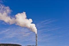 从烟囱的蒸汽反对深蓝天空 库存照片