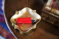 烟灰缸黄铜打火机红色圆桌 免版税图库摄影