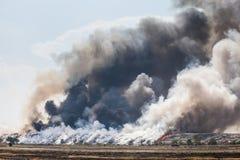 烟灼烧的垃圾堆  图库摄影