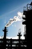 烟窗剪影在石油化工厂中 免版税库存图片