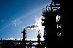 烟窗剪影在石油化工厂中 免版税库存照片