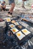 烟肉和鸡蛋或者蟾蜍在开放阵营火被烹调的孔 免版税库存照片