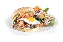 烟肉和鸡蛋汉堡包和沙拉 免版税库存图片