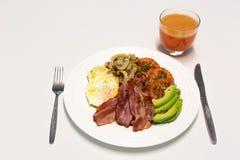 烟肉和鸡蛋烹调了早餐用苹果汁 免版税库存照片