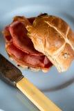 烟肉有十字架形的圆形圣糕和生锈的刀子在圆的板材 库存图片