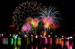 烟花庆祝和城市夜点燃背景 免版税库存图片
