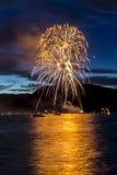 烟花庆祝在水的晚上 图库摄影