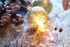 烟花或电闪烁发光物在手中在圣诞节装饰品杉木锥体 免版税库存图片