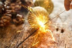 烟花或电闪烁发光物在手中在圣诞节装饰品杉木锥体 免版税图库摄影
