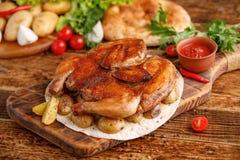 烟草鸡与装饰被烘烤的年轻土豆 在木背景的开胃静物画 免版税库存图片