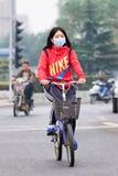 烟雾的面孔被掩没的女性骑自行车者覆盖了城市,北京,中国 免版税库存图片