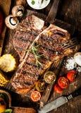 烤丁骨牛排在一个土气厨房里 免版税库存图片