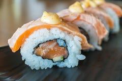 烤三文鱼寿司卷,在黑陶瓷的日本食物样式 免版税库存图片