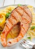 烤三文鱼海鲜晚餐在扁面条的 库存图片