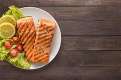 烤三文鱼用柠檬,在木背景的蕃茄 复制 库存图片