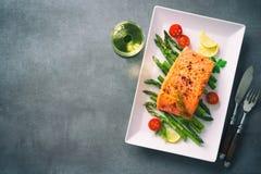 烤三文鱼装饰用绿色芦笋和蕃茄 库存照片