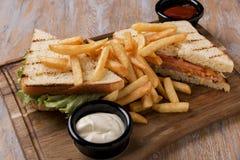 烤三明治用蕃茄火腿乳酪和炸薯条在一个委员会用调味汁 库存照片