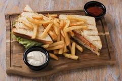 烤三明治用蕃茄火腿乳酪和炸薯条在一个委员会用调味汁 库存图片