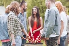 烤与朋友的愉快的妇女shashlik在生日聚会期间在庭院里 库存照片